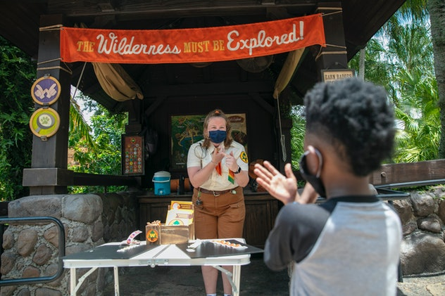 A cast member offers a young guest some hand sanitizer.