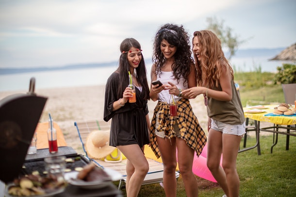 Three friends hang out at a barbecue outside, while laughing at something on their phones.