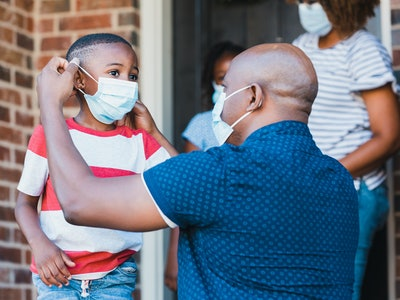 dad putting face mask on little boy