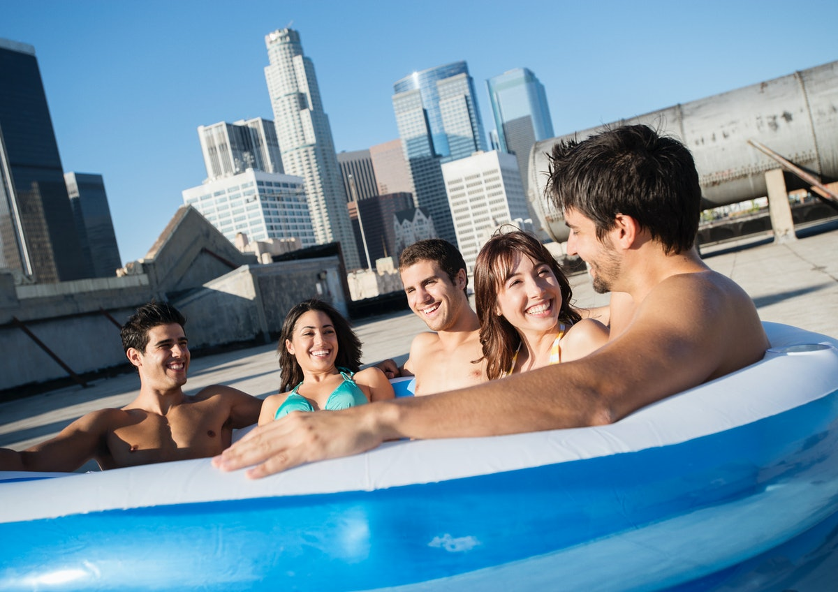 A group of friends sit in an inflatable pool on the roof.
