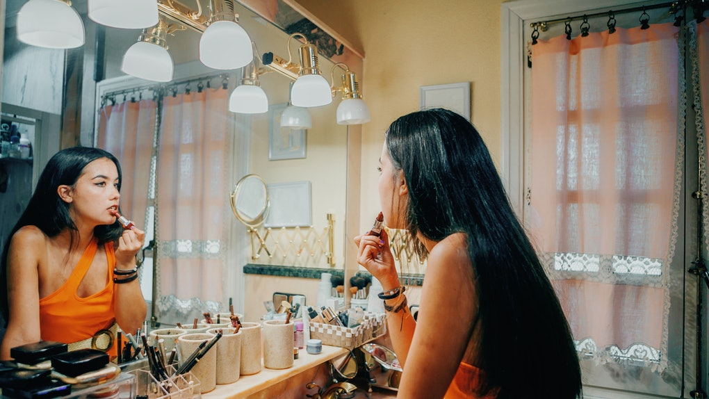 A young woman does her makeup in a vintage-looking bathroom mirror.