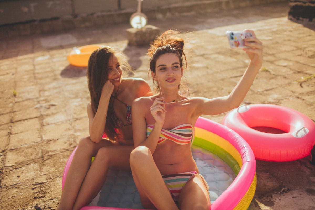 Two friends snap a selfie, while sitting in an inflatable pool.