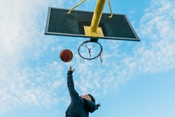 A person throws a basketball. These are team sports you can play by yourself during quarantine.