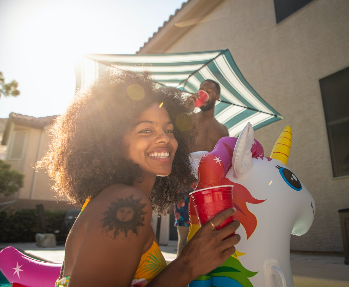 A happy woman sits on a unicorn pool float, while hanging in her backyard during the summer.