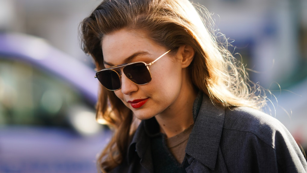 Gigi Hadid steps out in a gray blazer and aviator sunglasses.
