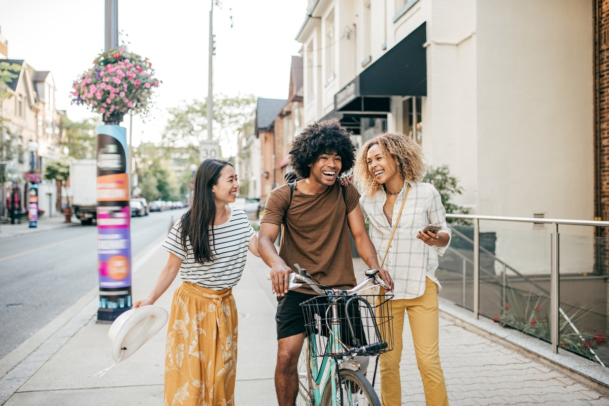 Three friends go bike riding in the city on a summer day.