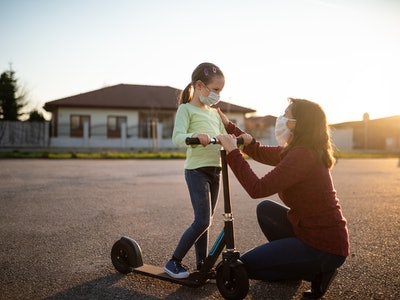 mom and daughter on scooter with face mask