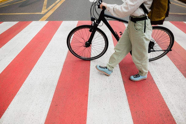 A young woman walks across a white and red crosswalk with her bike on a summer day.