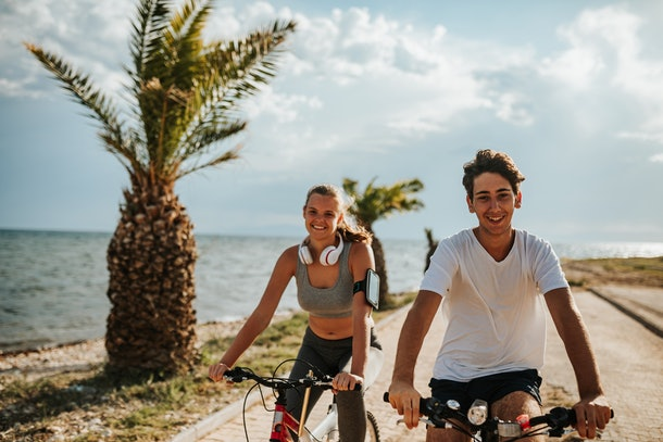 A young couple goes biking next to the ocean at sunset, and smiles for the camera.