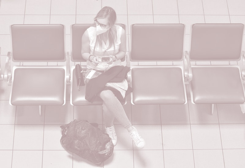 A woman with a face mask sits in a travel terminal. Self-quarantine is necessary when you travel between many U.S. states right now.
