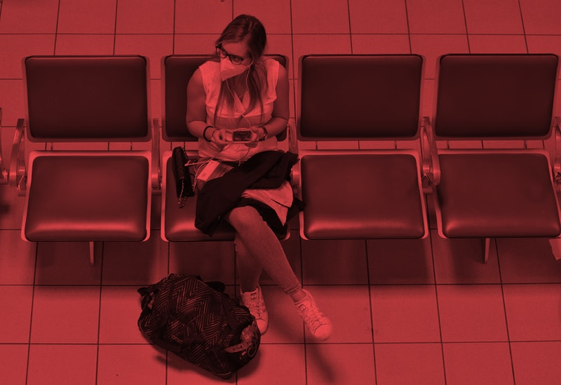 A woman with a face mask sits in a travel terminal. Self-quarantine is necessary when you travel bet...
