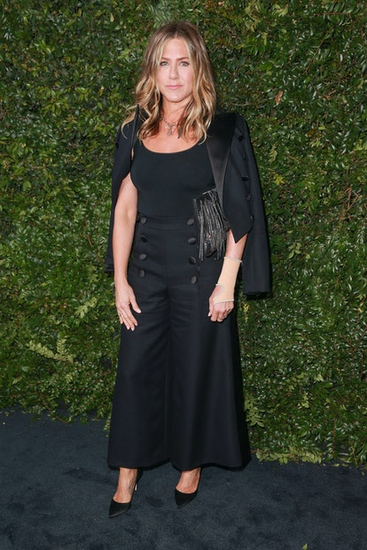 Jennifer Aniston wearing a black Chanel outfit at a 2018 Chanel party.