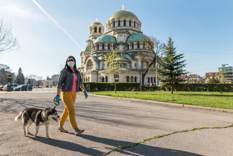 A woman walks her dog while wearing a mask. Fear of outside spaces may become more common during the pandemic, experts say.