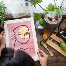 A woman holds a pink abstract painting in a windowsill garden. These seven myths about bipolar disorder, debunked by doctors, are ones you need to stop believing.