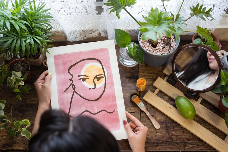 A woman holds a pink abstract painting in a windowsill garden. These seven myths about bipolar disor...