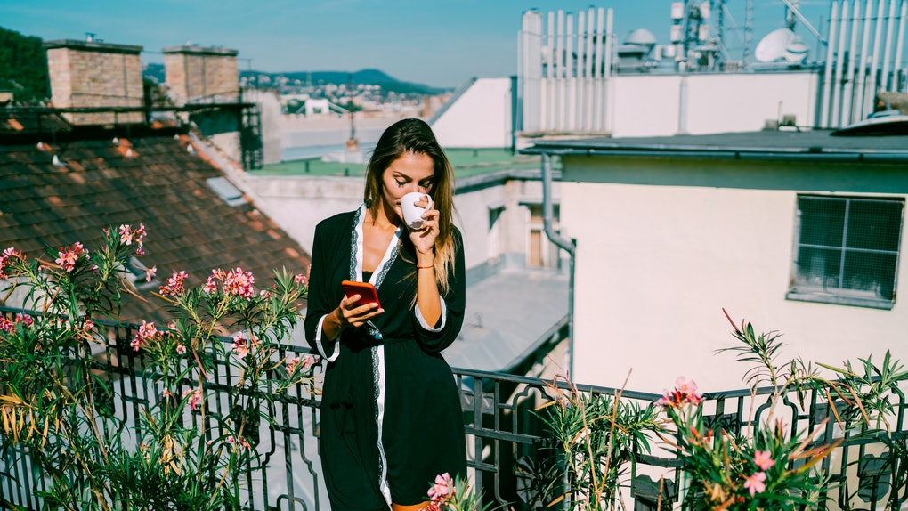 A young woman sips on coffee while standing on her balcony that's covered with plants.