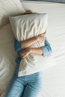 A woman with a pillow over her face. Experts explain how to get control of your stress dreams.