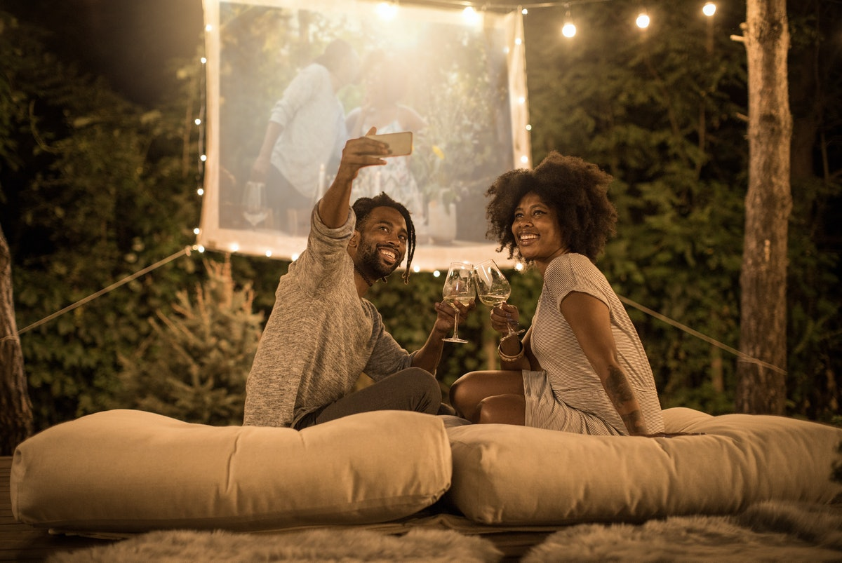A couple takes a selfie while holding glasses of wine and watching a movie in their backyard.