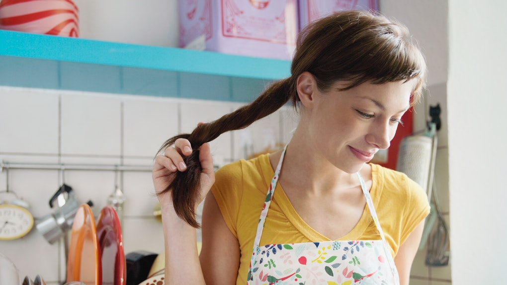 A woman twirls her hair, while looking through a cookbook in her kitchen.