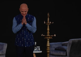 Jeff Bezos bows on stage during a trip to India.