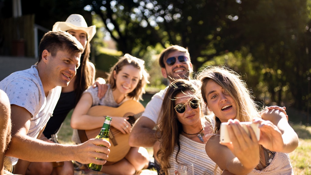 A group of friends pose for a selfie during a backyard picnic.