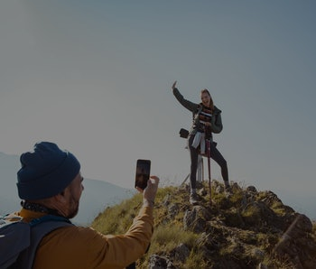 A woman is smiling and standing atop a hill while posing for a photo a man is taking of her from afar..