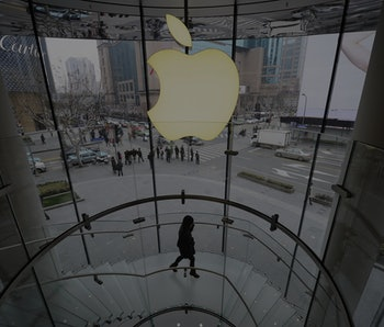 A person is seen walking down the stairs beneath the Apple logo in one of the company's retail stores.