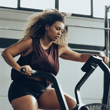 A person with natural curly hair works hard on an elliptical. Motivating yourself to work out by bea...