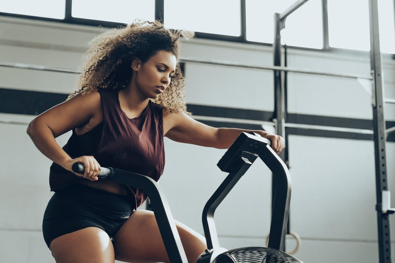 A person with natural curly hair works hard on an elliptical. Motivating yourself to work out by beating yourself up won't help you feel better.