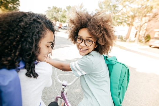 kid on bike with backpack and friend on way to school