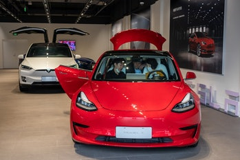 A Tesla Model 3, with a Model X behind.