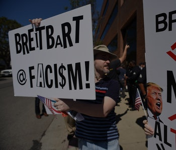 Protestors hold up signs equating Breitbart to fascism and fake news.
