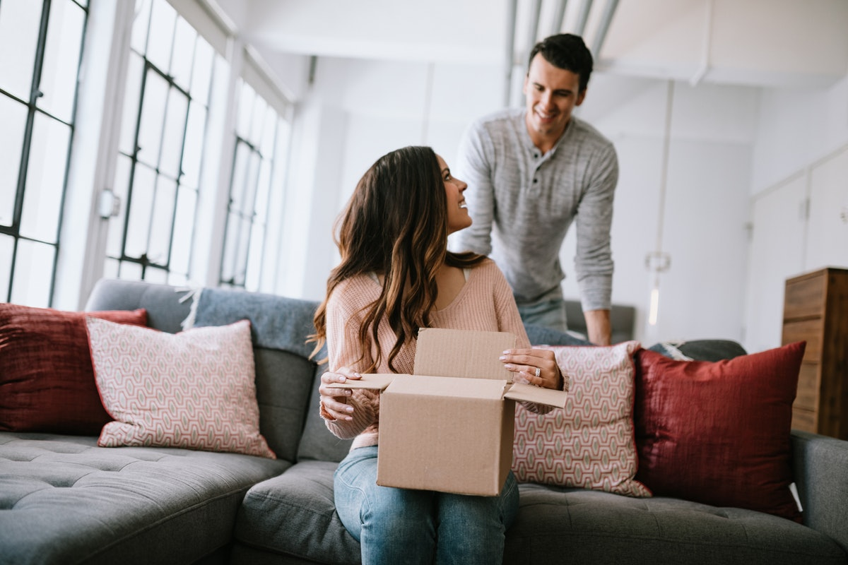 A young couple smiles while opening up a gift box on their couch.