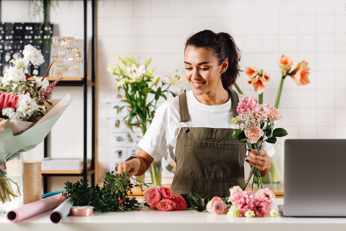 A young woman puts together a fresh flower bouquet while wearing an apron.