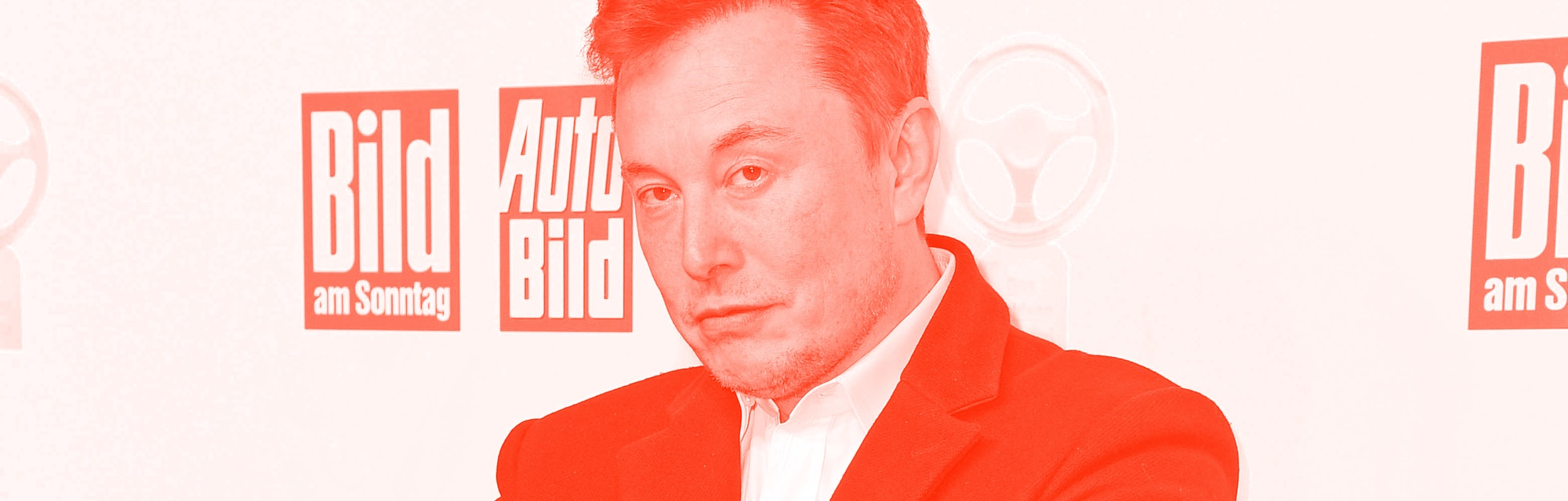 Elon Musk with his arms crossed and his eyebrow raised.