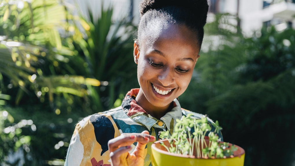 A happy woman in a floral printed button-down tends to her potted plant outside in the sunshine.