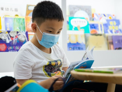 kid read book with face mask