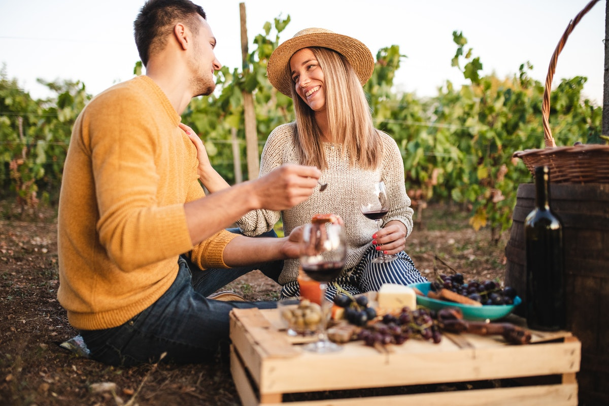 A couple sits outside with their wine and cheese board.