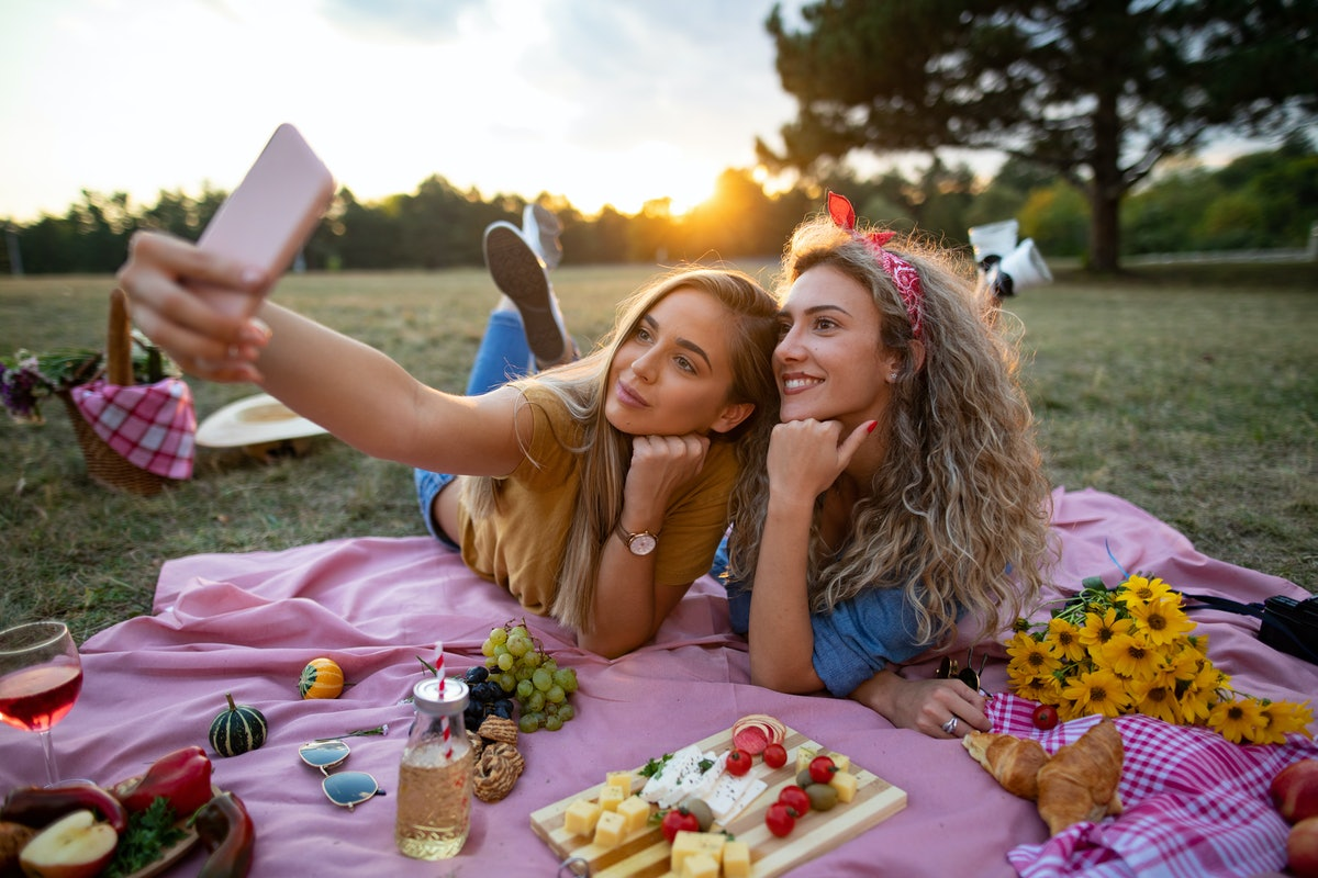 Two friends take a selfie during their wine and cheese board picnic outside.