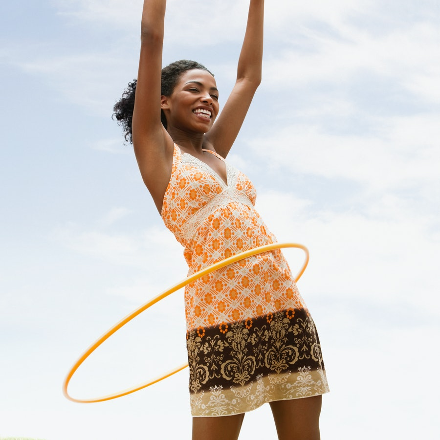A woman hula hoops. These nostalgic outdoor activities make excellent workouts as an adult.