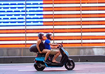 A man and woman can be seen on a Revel moped in front of the United States flag.