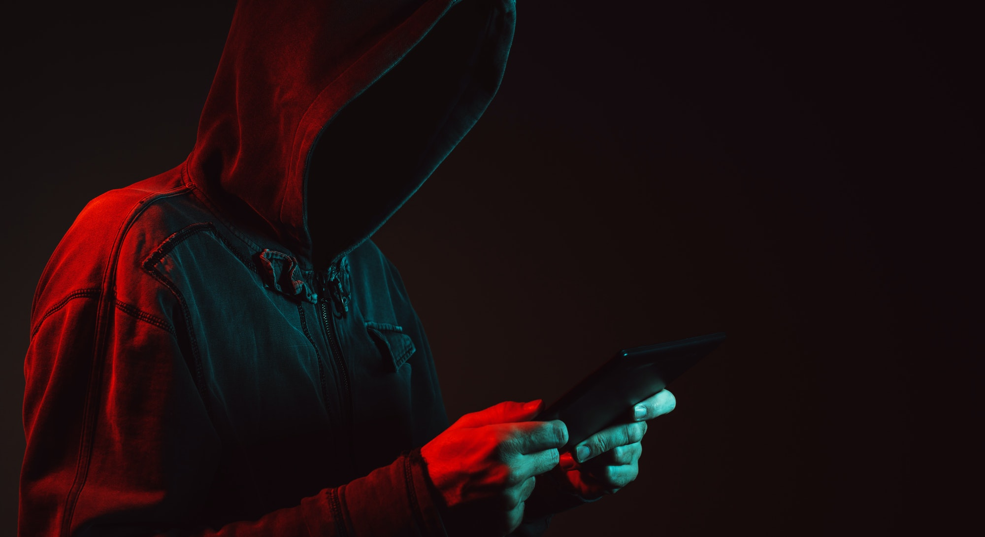A hooded man holding a phone. Ransomware attack.