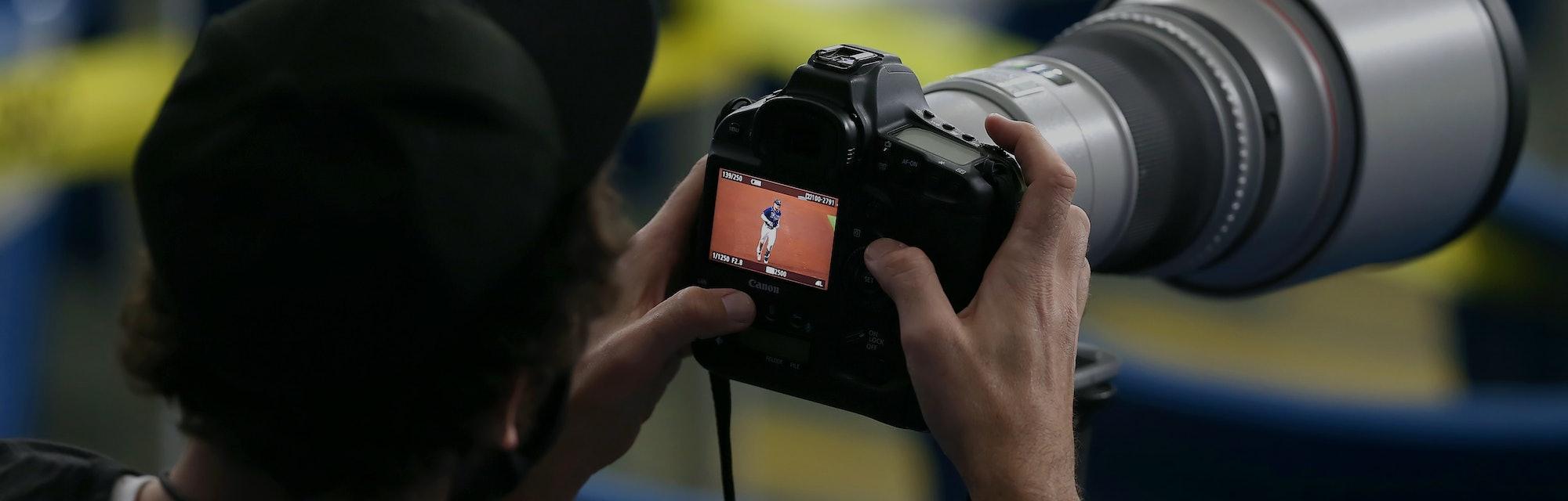 Photographer holding a DSLR camera.