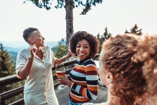 A young Black woman smiles and hangs out with her friends while holding a glass of rosé.