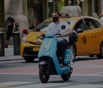 A man wearing a white shirt can be seen riding a Revel moped. Behind him there is a New York taxi.