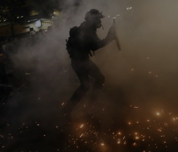 An armed guard can be seen walking through a fog, presumably teargas.