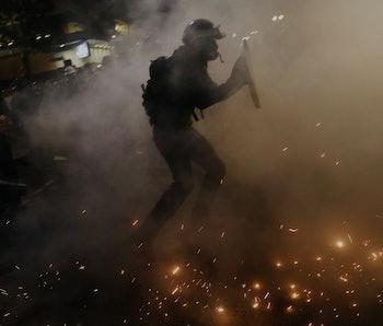 An armed guard can be seen walking through a fog, presumably teargas.
