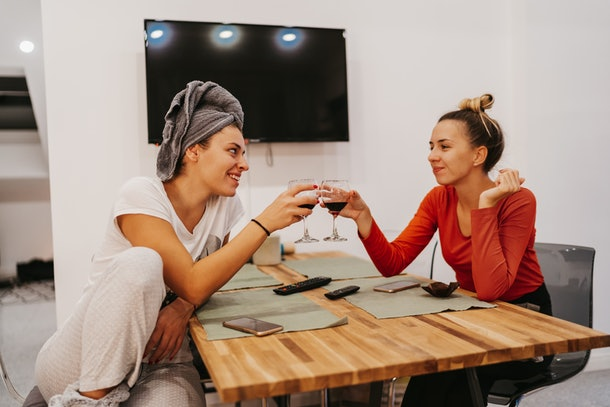 Two roommates sit at their kitchen table at the end of the day, and clink their glasses of red wine.