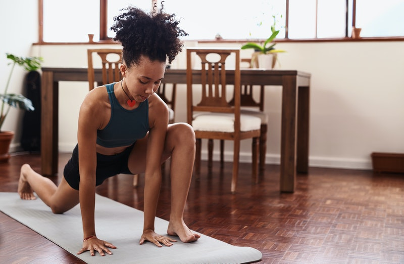 A woman does a lunch in her living room. These quiet workouts are good options for when your neighbors are asleep.