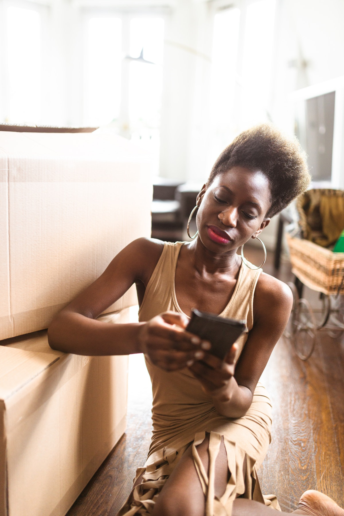 A young Black woman sits next to cardboard boxes on her apartment floor and texts on her phone.
